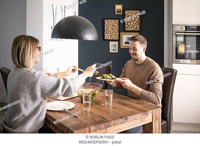 Couple eating salad at dining table at home