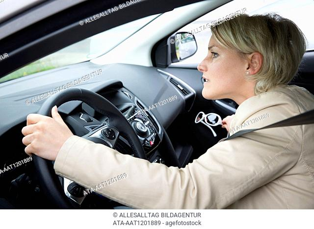 Female car driver takes glaces out of the glove box