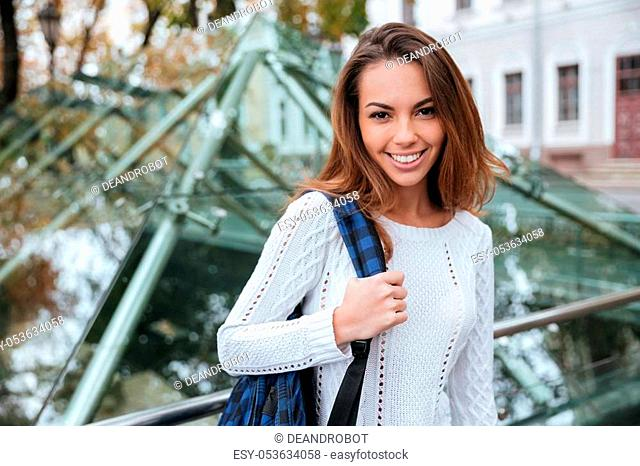 Portrait of cheerful attractive young woman with backpack in the city