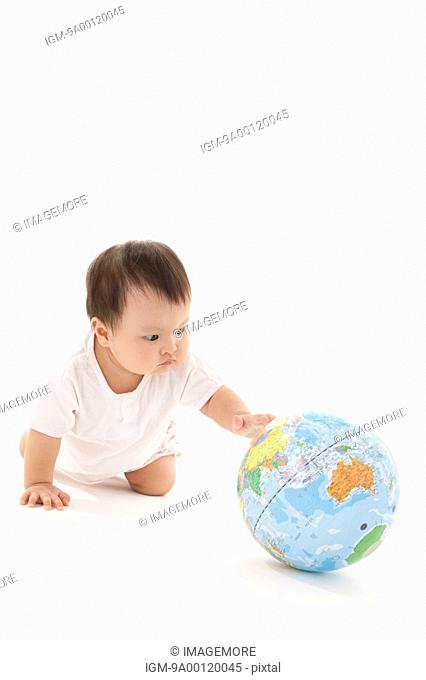 Baby girl crawling on floor and reaching for a globe