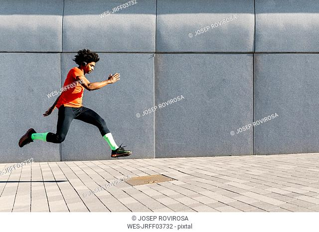Young man jumping in front of a gray wall in the city, listening to music
