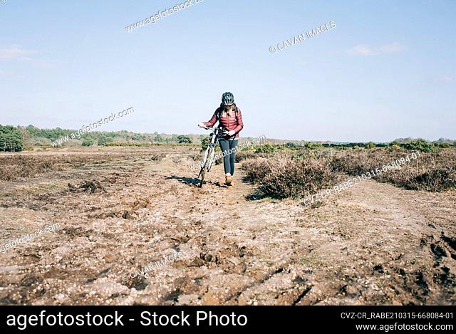 woman walking with her bike whilst out mountain biking in England