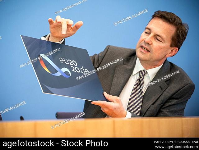 29 May 2020, Berlin: Steffen Seibert, spokesman for the German government, shows the logo of the German EU Council Presidency. From 01.07