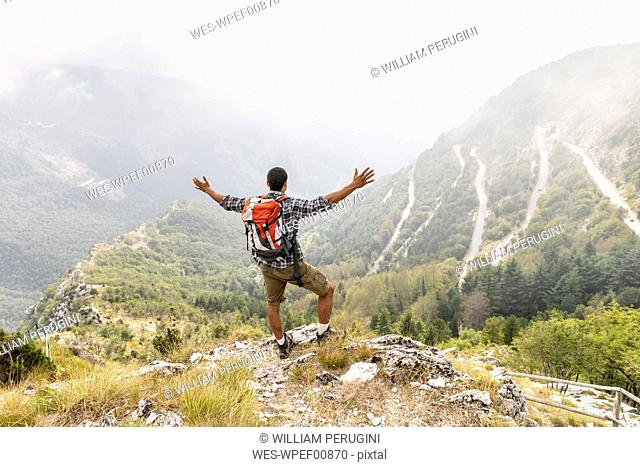 Italy, Massa, man hiking and enjoying the view in the Alpi Apuane