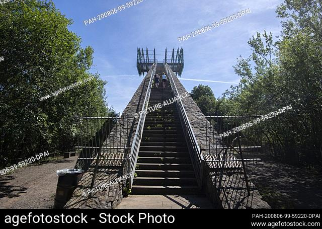 05 August 2020, Lower Saxony, Rinteln: A couple climbs the lookout point Jahrtausendblick at the former amusement park Steinzeichen Steinbergen in the district...