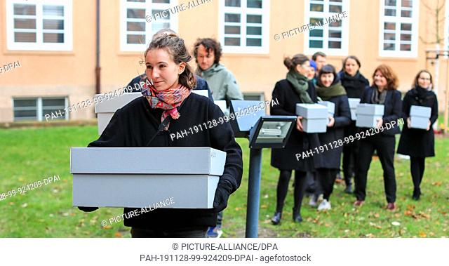 28 November 2019, Saxony, Leipzig: Museum staff carry crates containing the bones of indigenous Australians in the courtyard of the Grassi Museum as part of the...