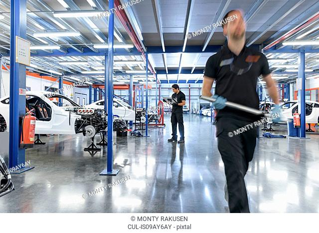 Engineers in construction area in racing car factory