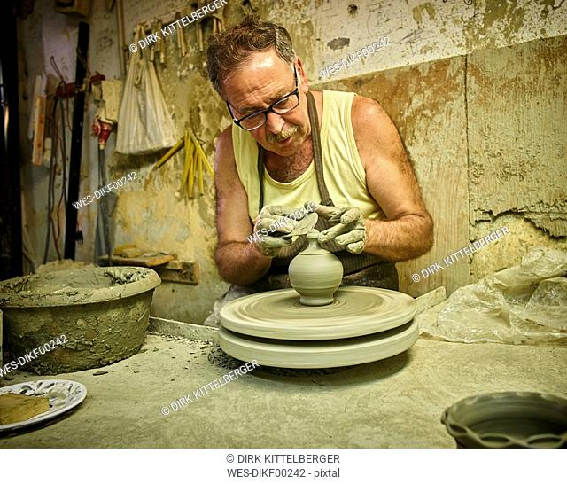 Potter in workshop working on earthenware vessel