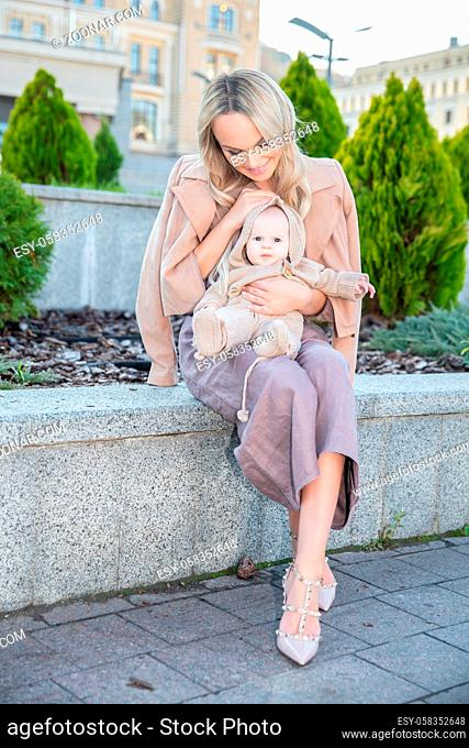 Charming happy mother with a small daughter in her arms sitting on the parapet