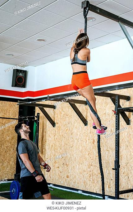 Man watching woman climbing a rope in gym