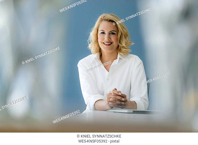 Portrait of smiling businesswoman sitting at table