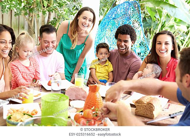 Group Of Families Enjoying Outdoor Meal At Home