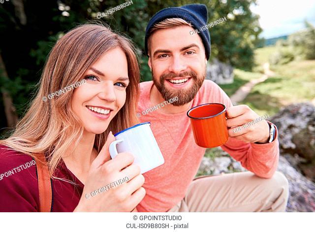 Portrait of couple holding enamel mugs looking at camera smiling, Krakow, Malopolskie, Poland, Europe