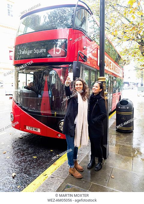 UK, London, two happy friends taking selfie with smartphone in front of red double-decker bus