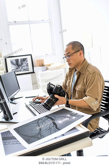 Korean photographer using computer at desk
