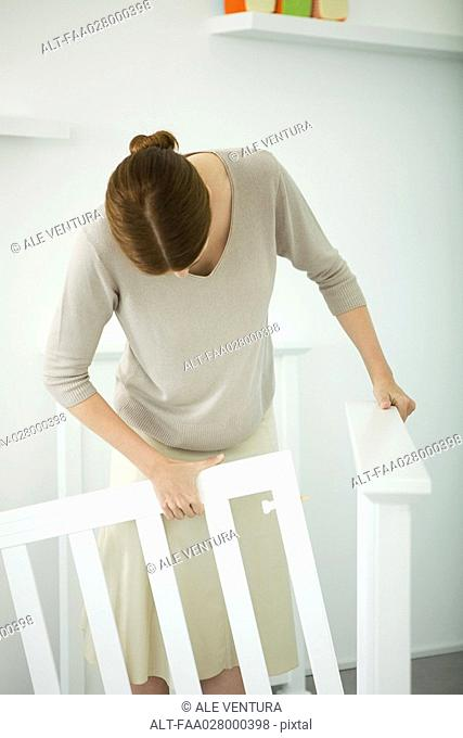 Woman standing in nursery, putting together baby crib