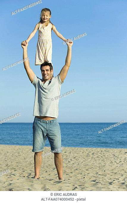 Girl standing on father's shoulders at the beach