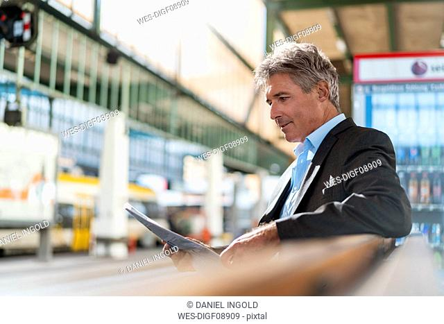 Mature businessman reading newspaper on station platform