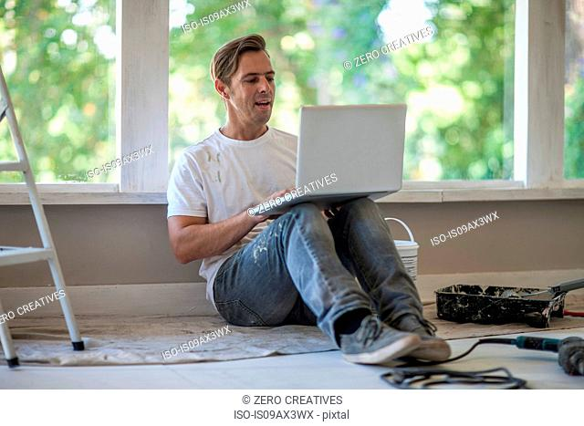 Builder using laptop on floor