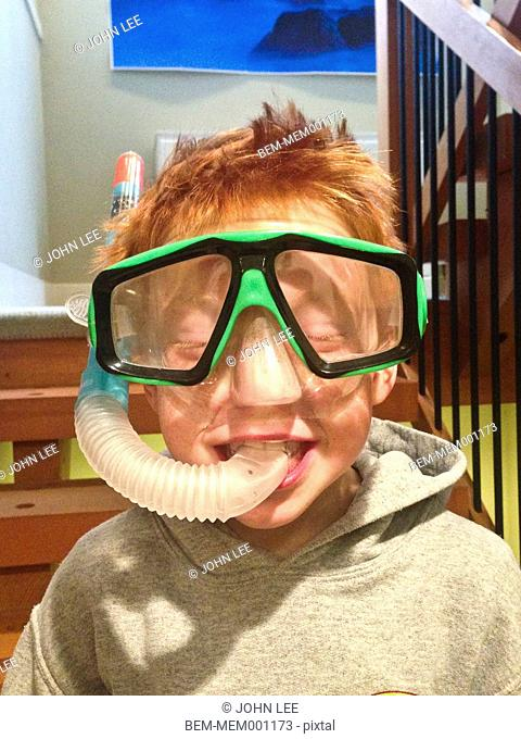 Caucasian boy wearing snorkel indoors