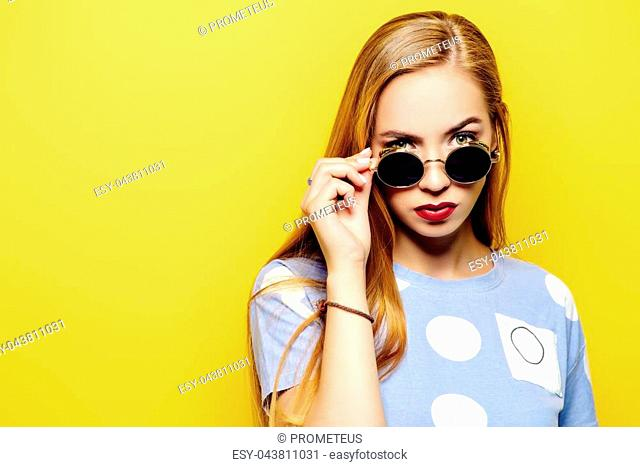 Serious young woman is looking over the sunglasses on a yellow background. Optics, sunglasses
