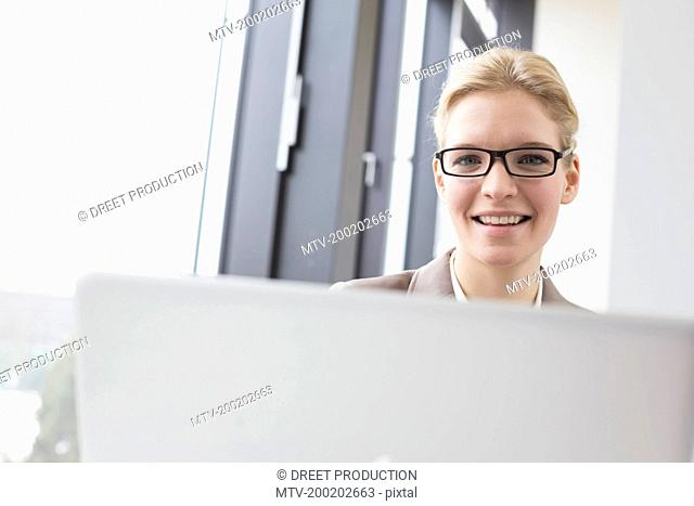 Portrait of businesswoman in office with laptop, smiling