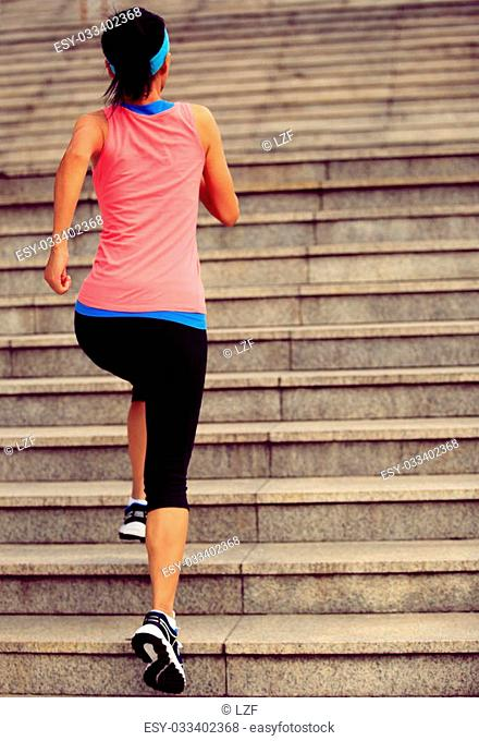 Runner athlete running on stairs. woman fitness jogging workout wellness concept