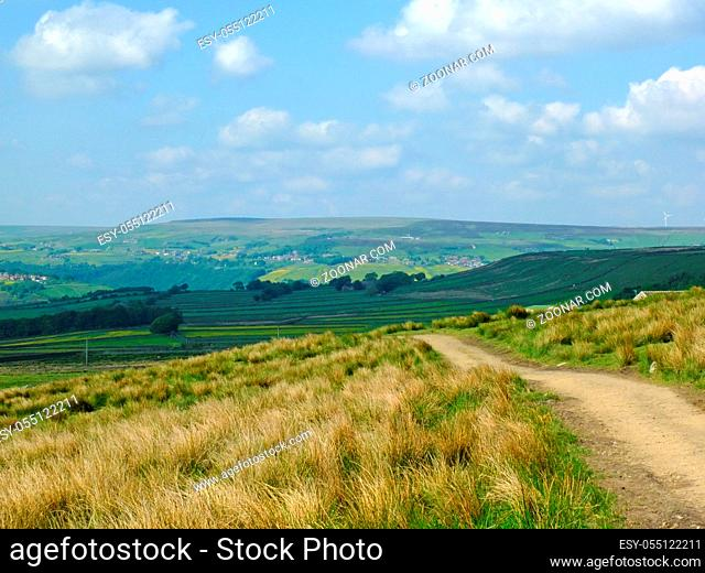 a long footpath running downhill in stoodley moor in yorkshire with fields and farms in the distance with the pennine hills on the horizon on a sunny summers...