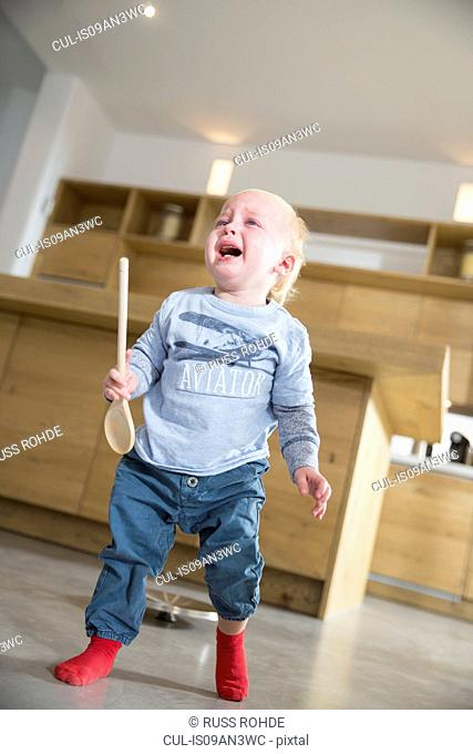 Male toddler holding wooden spoon and crying in dining room