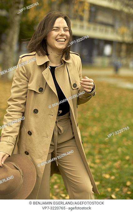 laughing fashionable woman walking outdoors in park in autumn, wearing coat, happy candid emotion, in Munich, Bavaria, Germany