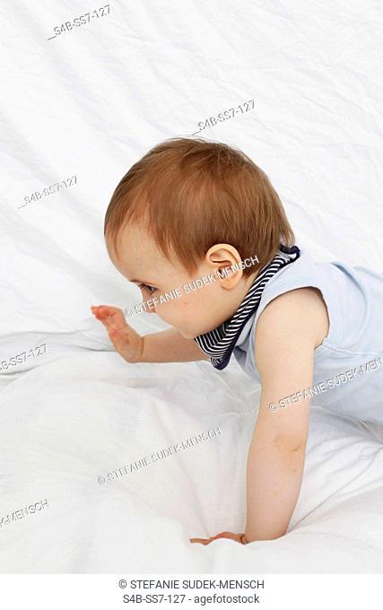 Toddler wearing undershirt in bed, Berlin, Germany