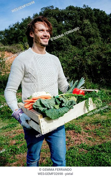 Man carrying crate with freshly harvested vegetables from his vegetable garden