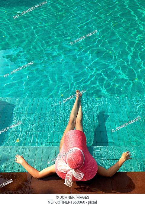Woman resting at edge of swimming pool