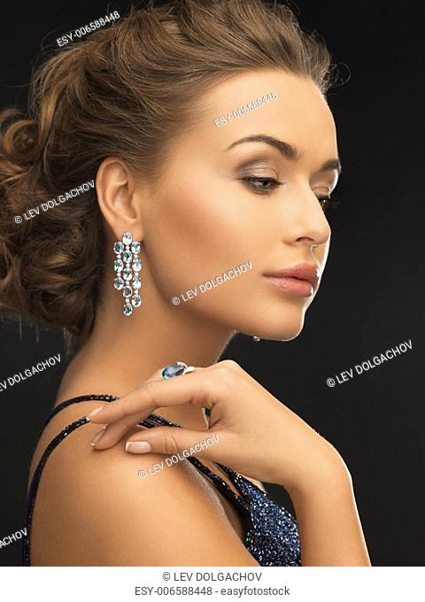 woman in evening dress wearing diamond earrings and ring