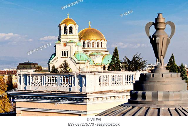 A view of golden domes st. Aleksander Nevski cathedral in Sofia, Bulgaria through a detail on a roof of a building. Horizontal image
