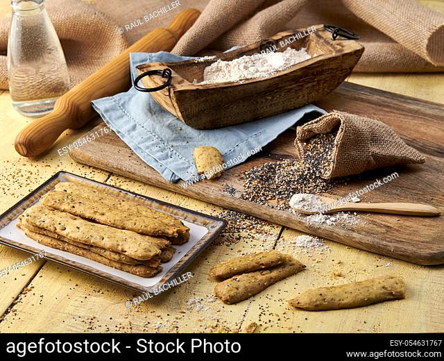 homemade bread sticks with ingredients in yellow plate and wood background