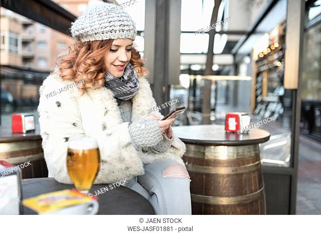 Young woman using cell phone on terrace of a pub in winter