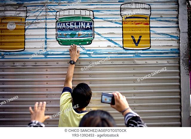 A blind student touches a truck before taking a picture of it during a photography workshop for the blind and visually impaired