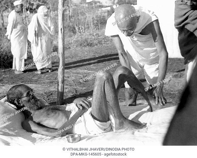Mahatma Gandhi attending to the leper patient Sanskrit scholar Parchure Shastri at Sevagram Ashram , 1939 , a visitor NO MR