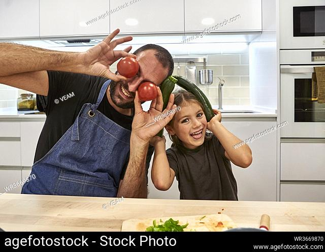 Cheerful father and daughter playing with tomatoes and zucchinis in kitchen