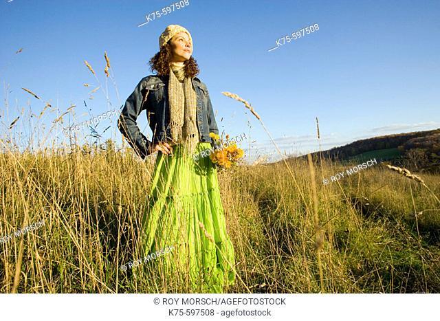 Woman standing in field on hilltop