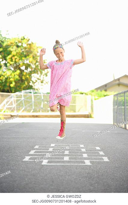Girl (10-12) in pink dress jumping