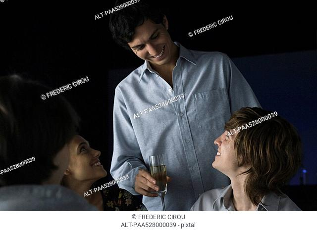 Man holding glass of champagne talking to friends