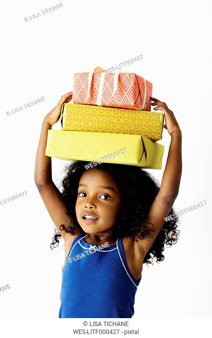 Portrait of smiling little girl carrying three presents on head in front of white background