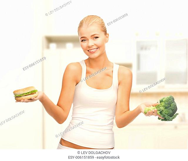 diet and fitness concept - sporty woman with broccoli and hamburger