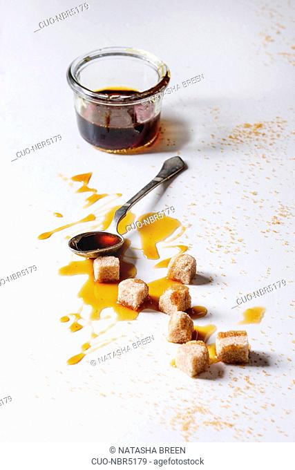 Homemade liquid transparent brown sugar caramel in glass jar with spoon and cane sugar cubes over white marble background. Copy space