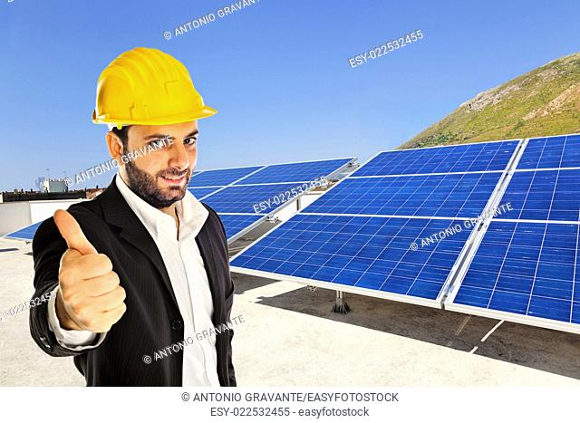 Businessman with big solar panel and yellow helmet