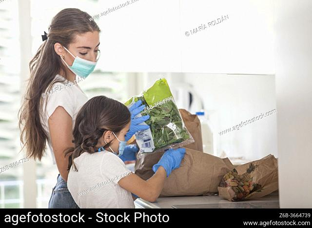 mother and daughter wears masks and gloves while taking out groceries