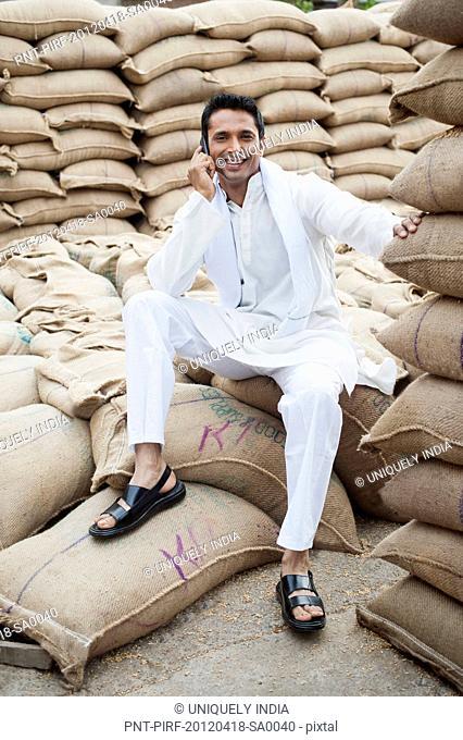 Man sitting on a sack of wheat and talking on a mobile phone in a warehouse, Anaj Mandi, Sohna, Gurgaon, Haryana, India