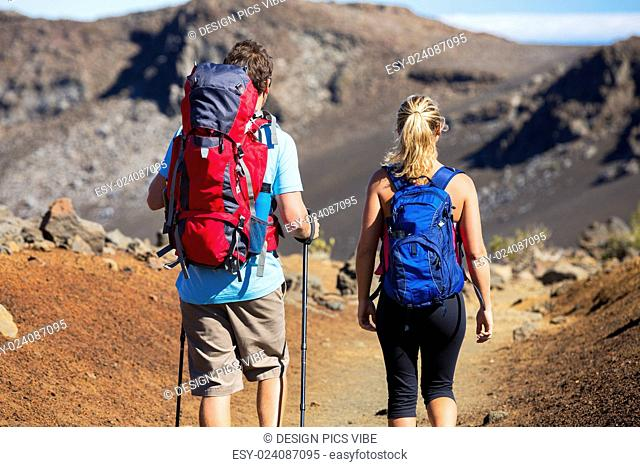 Hiking in the mountains. Athletic couple with backpacks enjoying hike outdoors